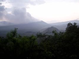Vista desde la parte superior de la reserva forestal al volcán principal con la niebla de la mañana